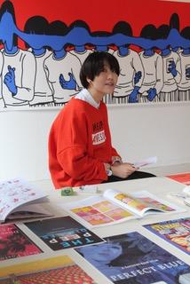 Yuqing Wang devant l'une de ses oeuvres